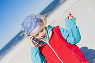 Germany, Mecklenburg-Western Pomerania, Ruegen, Schaabe, Boy on cell phone at the beach - MJF001221