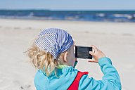 Germany, Mecklenburg-Western Pomerania, Ruegen, Schaabe, Boy holding cell phone at the beach - MJF001223