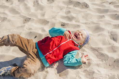Germany, Mecklenburg-Western Pomerania, Ruegen, Schaabe, Boy lying in sand on beach - MJF001227