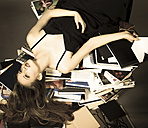 Portrait of young woman lying on pile of books - FC000218