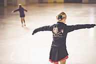 Two young female figure skaters on ice rink at competition - MJF001271