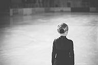 Young female figure skater standing on ice rink at competition, back view - MJF001275