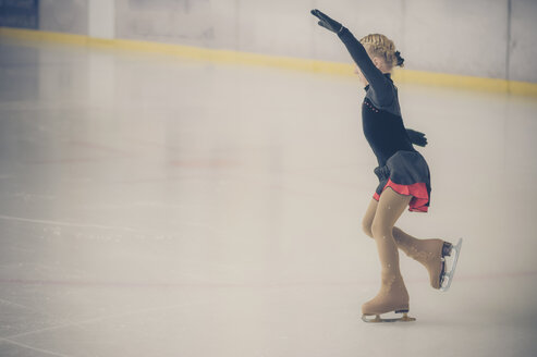 Young female figure skater moving on ice rink at competition - MJF001278
