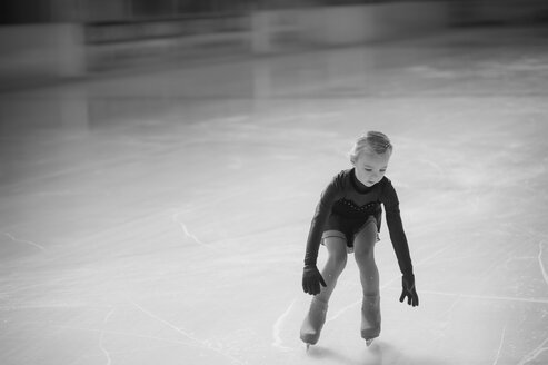 Young female figure skater moving on ice rink at competition - MJF001280
