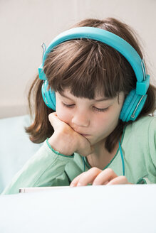 Portrait of little girl with headphones and smartphone - LVF001306