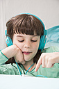 Portrait of little girl with headphones using smartphone - LVF001310