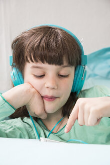 Portrait of little girl with headphones using smartphone - LVF001310