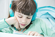 Portrait of little girl with headphones using smartphone - LVF001311