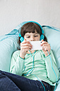 Portrait of little girl with headphones using smartphone - LVF001316