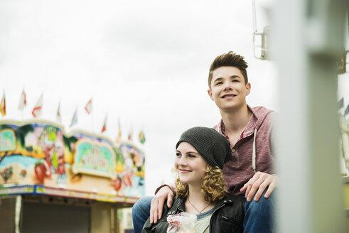 Portrait of happy teenage couple at fun fair - UUF000660