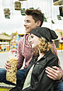 Portrait of happy teenage couple with popcorn at fun fair - UUF000659