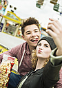 Portrait of teenage couple with popcorn photographing themself at fun fair - UUF000630