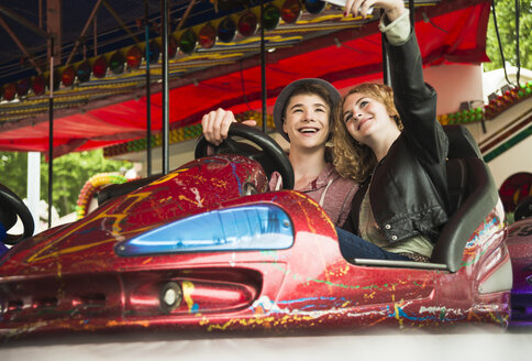 Teenage couple sitting in bumper car photographing themself with smartphone - UUF000616