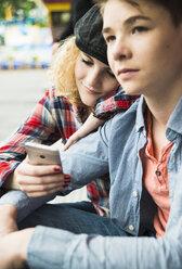 Portrait of teenage couple using smartphone at fun fair - UUF000644