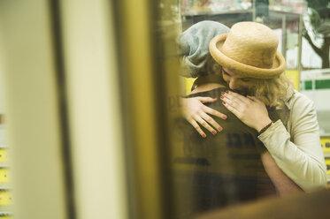 Teenage girl embracing her boyfriend at fun fair - UUF000619