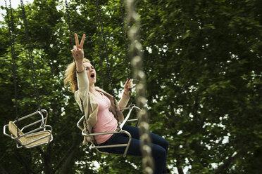 Teenage girl on chairoplane at fun fair - UUF000673