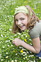 Portrait of laughing girl crouching on  flower meadow with magnifying glass - STB000169