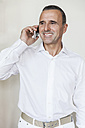 Portrait of smiling senior doctor telephoning with smartphone - MFF001125