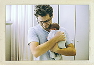 Father holding his newborn baby in hospital room - MFF001097