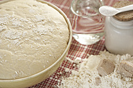 Bowl of raw yeast dough and ingredients of yeast dough on cloth, partial view - SABF000022