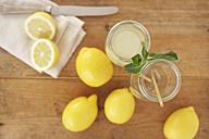 Carafe of lemon juice, sliced and whole lemons on wood, elevated view - SABF000028