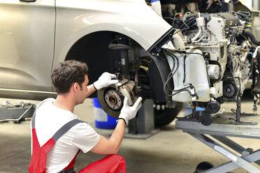 Car mechanic in a workshop working at car - LYF000018