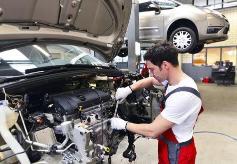 Car mechanic in a workshop working at car - LYF000025