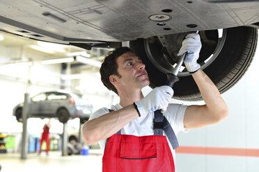 Car mechanic in a workshop working at car - LYF000033