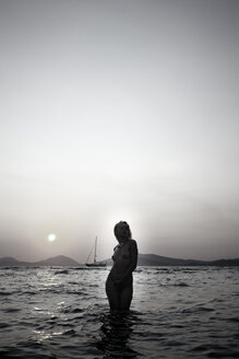 Naked young woman standing in the sea by twilight - AJF000042