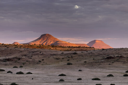Africa, Namibia, Damaraland, view to grassland and volcanos by sunset - HLF000603