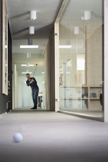 Business man playing golf in corridor of modern office - FKF000496