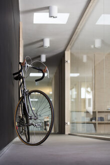 Racing cycle standing in corridor of modern office - FKF000500