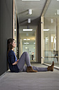 Portrait of business woman sitting on ground in corridor of office - FKF000502