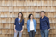 Group picture of three creative business people in front of wood shingle panelling - FKF000517