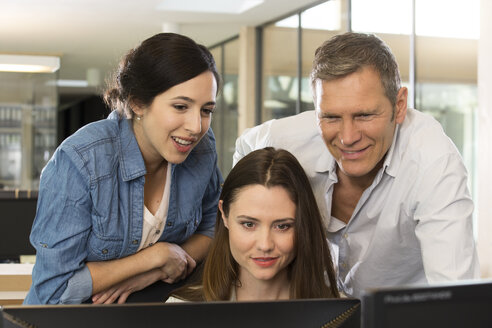 Portrait of three business people looking at computer - FKF000545