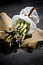 Bunch of green asparagus in white paper bag on jute and dark wood - MAEF008335