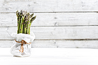 Bunch of green asparagus standing in white paper bag in front of white wood - MAEF008336