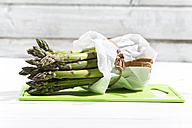 Bunch of green asparagus in white paper bag lying on green chopping board and white wood - MAEF008338