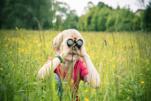 Little boy sitting on meadow watching something with binocular - SARF000658