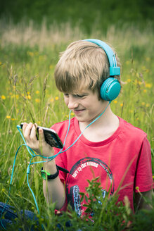 Portrait of boy with smartphone and headphones on meadow - SARF000659