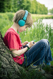Portrait of boy with smartphone and headphones leaning on tree - SARF000687