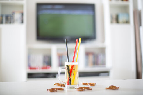 Beer mug with three drinking straws in German national colours and pretzels in front of television with empty soccer field - SARF000666