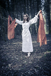Portrait of a young woman standing in forest with outstretched arms holding clothes - VTF000254
