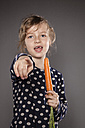Portrait of little girl using carrot as a microphone - OJF000021