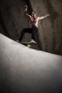 Skateboarder performing trick at skateboard park - KJ000298