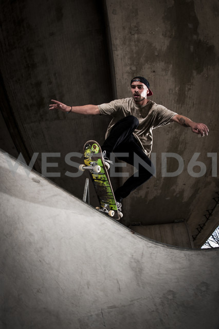 Skateboarder performing trick at skateboard park - KJ000300