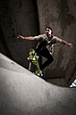 Skateboarder performing trick at skateboard park - KJ000300