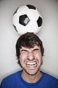 Young man balancing soccer ball on head - JATF000719