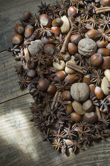 Star anise, walnuts, hazelnuts, almonds and cinnamon sticks on wood, partial view - ASF005405