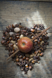 Heart shaped of star anise, nuts and cinnamon sticks with apple pierced of cinnamon sticks on wood - ASF005407